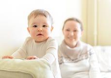 Jogos do bebê com a mãe no sofá fotografia de stock