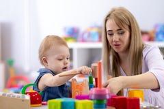 Jogos do bebê com mãe ou professor no berçário foto de stock royalty free