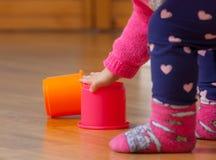 Jogos do bebê da criança com copos coloridos Fotografia de Stock Royalty Free