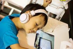 Jogos do Internet do computador do jogo da criança e auriculares asiáticos do desgaste Imagens de Stock Royalty Free