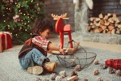 Jogos do menino com cones do pinho fotografia de stock