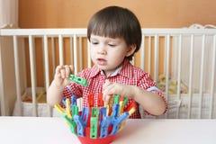 Jogos do rapaz pequeno com pinos de roupa Imagem de Stock