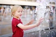 Jogos do rapaz pequeno no quadrado entre os jatos de água na fonte no dia de verão ensolarado imagens de stock