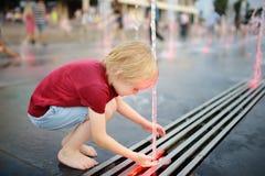 Jogos do rapaz pequeno no quadrado entre os jatos de água na fonte na noite do verão fotografia de stock royalty free