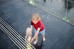 Jogos do rapaz pequeno no quadrado entre os jatos de água na fonte na noite do verão imagem de stock royalty free