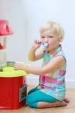 Jogos engraçados da menina da criança em idade pré-escolar com cozinha do brinquedo Foto de Stock Royalty Free