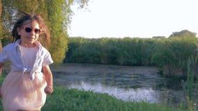 Jogos exteriores das crianças, crianças que correm e que jogam a captura no luminoso na vila vídeos de arquivo