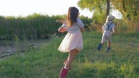 Jogos exteriores, menino pequeno e menina jogando a captura e o corredor no luminoso no campo filme