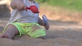 Jogos pequenos bonitos do bebê na praia com pá, ancinho e areia filme