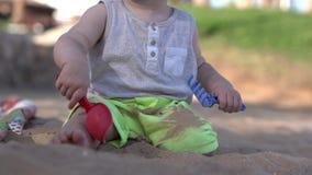 Jogos pequenos bonitos do bebê na praia com pá, ancinho e areia video estoque