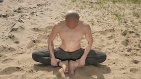 Jogowie siedzą w lotosowej pozyci na piasku zbiory
