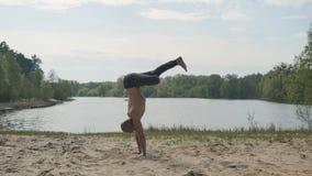 Jogowie utrzymują równowagę na rękach na piasku blisko rzeki zbiory wideo