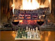 Jogue o vinho tinto bebendo da xadrez na frente de uma chaminé rujir Foto de Stock Royalty Free