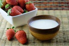 Jogurt in einer hölzernen Schüssel mit Erdbeeren lizenzfreies stockbild