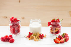 jogurt i jagoda w szkło słojach na bielu stole Zdjęcia Stock