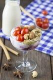 Jogurt mit Belagstomatenmandel-Acajounuss im Weinglas mit Lizenzfreie Stockfotos