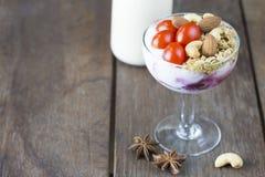Jogurt mit Belagstomatenmandel-Acajounuss im Weinglas mit Stockfoto