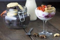Jogurt mit Belagstomatenmandel-Acajounuss im Weinglas mit Stockbild