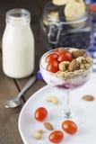 Jogurt mit Belagstomatenmandel-Acajounuss im Weinglas mit Milch auf Holztisch Lizenzfreie Stockfotos