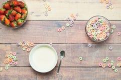 Jogurt mit Erdbeeren und Getreide zerstreute auf Holztisch Lizenzfreie Stockfotos