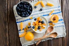 Jogurt mit frischen Blaubeeren, Corn Flakes und Aprikosen, Draufsicht Lizenzfreies Stockbild
