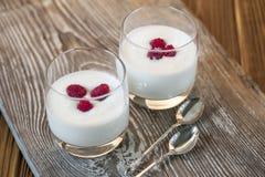 Jogurt mit Himbeere auf hölzerner grauer Tabelle stockfoto