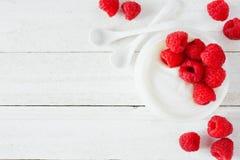 Jogurt mit Himbeeren, Draufsicht, Eckgrenze auf einem weißen hölzernen Hintergrund stockfotografie