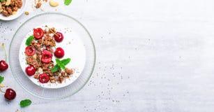 Jogurt mit Kirschen, Granola und Chia Seeds über hellem Hintergrund stockfotos
