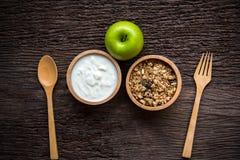 Jogurt mit muesli zum Frühstück morgens, Verlustgewicht und grüner Apfel nähren das Abnehmen für Frauen, alten hölzernen Hintergr Stockfoto