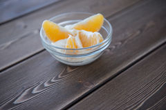 Jogurt und orange Scheiben in einem Glasteller auf einem Holztisch stockbilder