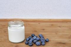 Jogurt w szklanym słoju i czarnych jagodach na drewnianym tle - horyzontalnym Fotografia Royalty Free