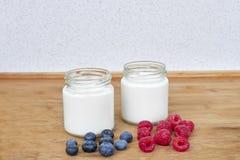 Jogurt w szklanym słoju, malinkach i czarnych jagodach na drewnianym tle, - horyzontalnym Obraz Stock