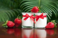 Jogurt z świeżymi truskawkami na tle obraz stock
