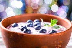 Jogurt z czarnymi jagodami i mennicą, bokeh tło Selekcyjny fo Obrazy Stock