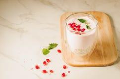 jogurt Jogurt z garnet i mennicą w szkle na drewnianej tacy i rozrzuconych granatowów ziarnach na białym marmuru stole kopia obrazy stock