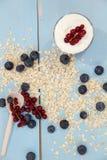 Jogurt z granola i świeżymi czarnymi jagodami w szklanym pucharze nad starym drewnianym tłem Rocznika skutek obraz stock