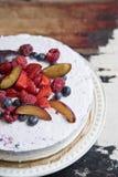 Jogurtkuchen mit Beeren auf einer Weinleseplatte auf dem Hintergrund einer alten Tabelle stockbilder