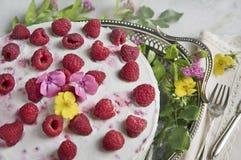 Jogurtkuchen mit Himbeeren auf einem alten Behälter mit Blumen, alter Gabel und Messer stockbild