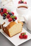 Jogurtpfundkuchen mit Glasur und frischen Beeren lizenzfreies stockfoto