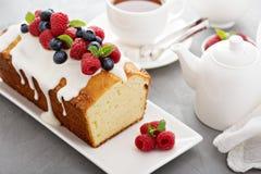 Jogurtpfundkuchen mit Glasur und frischen Beeren stockfoto