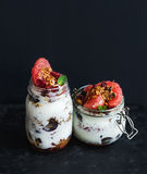 Jogurtu i owsa granola z winogronami, granatowiec, grapefruitowy w wysokim szklanym słoju fotografia stock