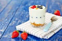 Jogurtu szkło z jagodami i musli na stole Zdjęcia Royalty Free