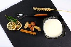 Jogurtu talerz, nowi liście, plasterki cytryna, banatka, dokrętki, kije cynamon i łyżka na czarnego iłołupka desce na białym plec obrazy royalty free