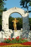 Johann Strauss park Vienna. Johann Strauss playing violin - a golden statue surrounded by art nouveau marble arch in Vienna city park (Stadtpark Royalty Free Stock Images
