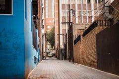 Johannesburg CBD alleyway z błękitem malował budynek w foregrou obraz stock