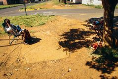 Woman sitting in a chair. Johannesburg , Gauteng / South Africa -August 02 2018 : african woman sitting in a chair in the sun by her pay phone waiting for royalty free stock images