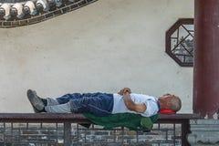 JOHANNESBURG/SÖDRA AFRICA-AUGUST 11 2019: En svart manarbetare vilar på en bänk Han är sova och ligga på hans arbetslag arkivfoton