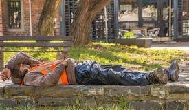 JOHANNESBURG/SÖDRA AFRICA-AUGUST 11 2019: En svart manarbetare vilar på en låg tegelstenvägg arkivfoto