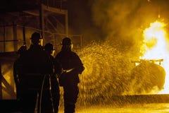 JOHANNESBURG, SÜDAFRIKA - Mai 2018 Feuerwehrmänner, die Wasser an brennendem Behälter während einer feuerbekämpfenden Schulungsüb lizenzfreies stockbild