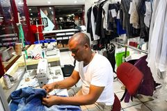 African Man repairing clothes at a Dry Cleaner. Johannesburg, South Africa - April 27 2011: African Man repairing clothes at a Dry Cleaner stock images